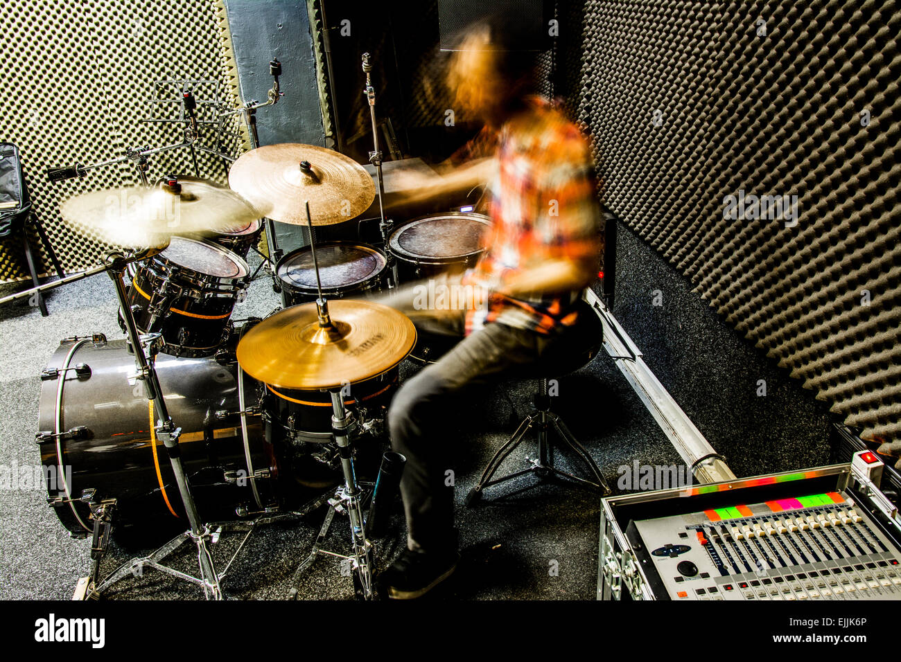 Drummer playing drums with power. - Stock Image