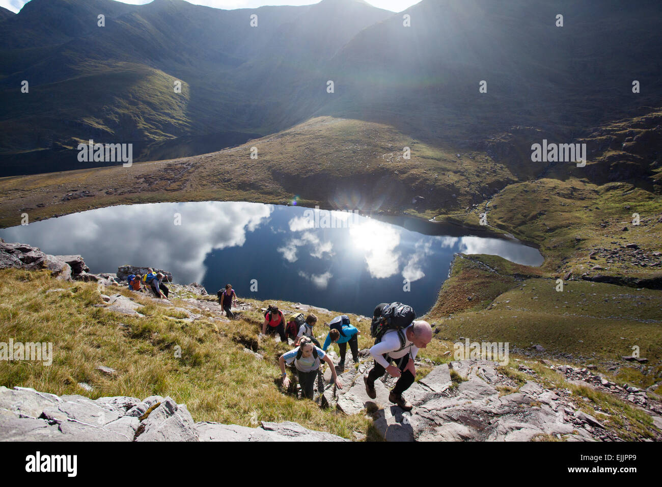 Walkers above Lough Gouragh on the ascent of Carrauntoohill, MacGillycuddy's Reeks, County Kerry, Ireland. - Stock Image