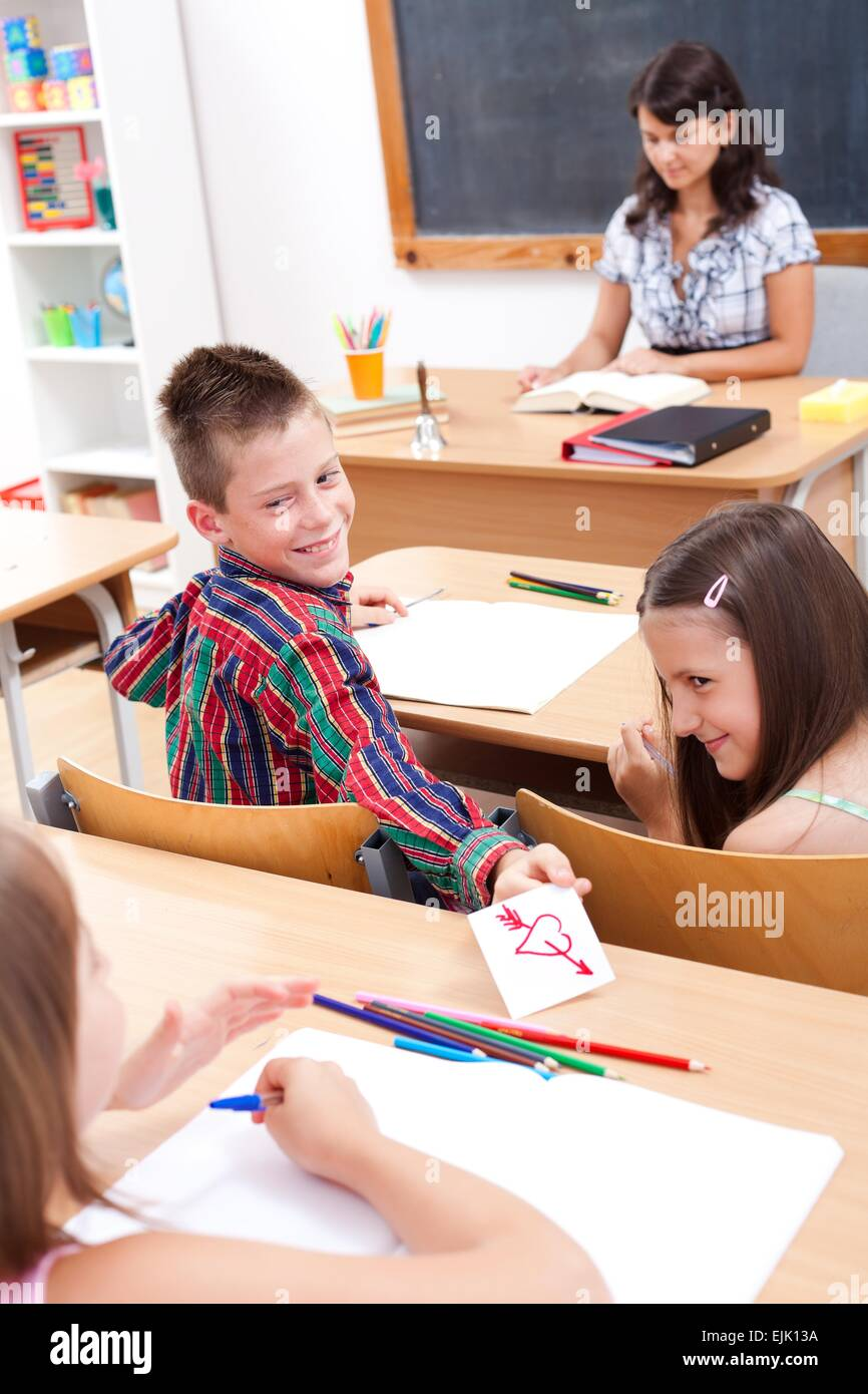 Cheerful elementary school boy giving love letter to his classmate while the teacher explains - Stock Image