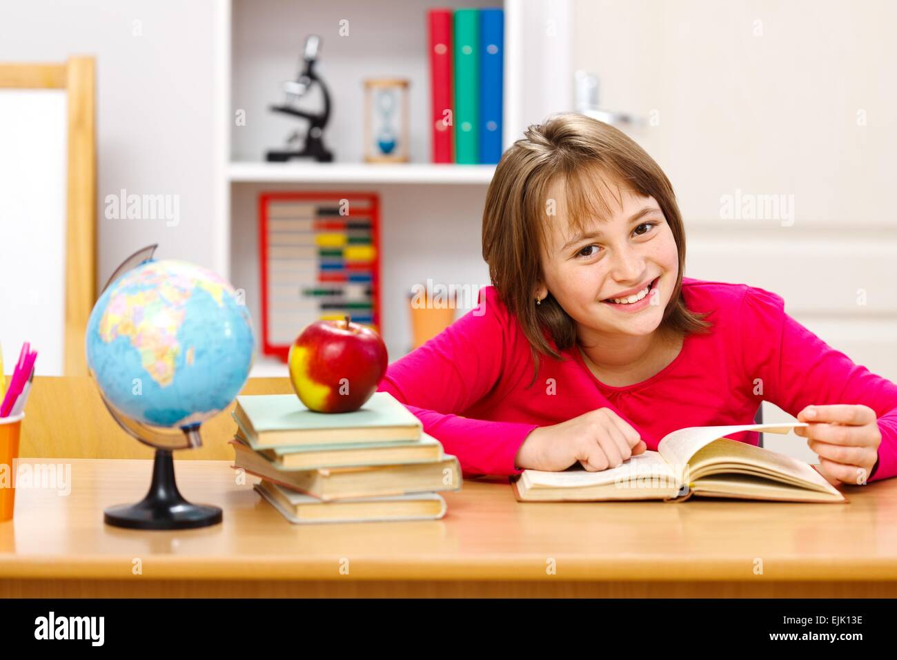 Pretty schoolgirl reading in classroom. Earth globe and whole apple on other stacked books - Stock Image