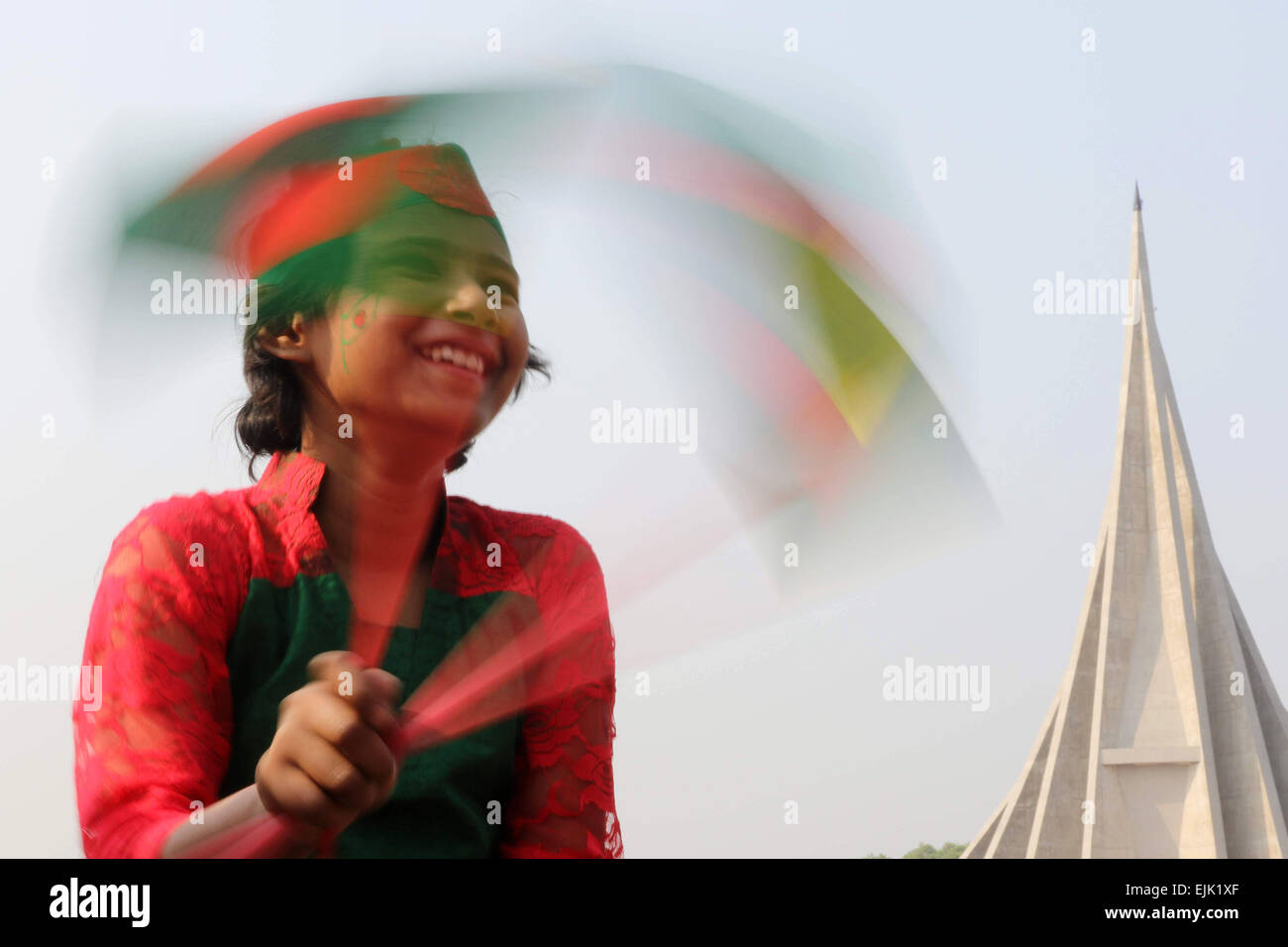 A Bangladeshi child holds a national flag as she stands in front the National Monument for the Martyrs of the Liberation - Stock Image