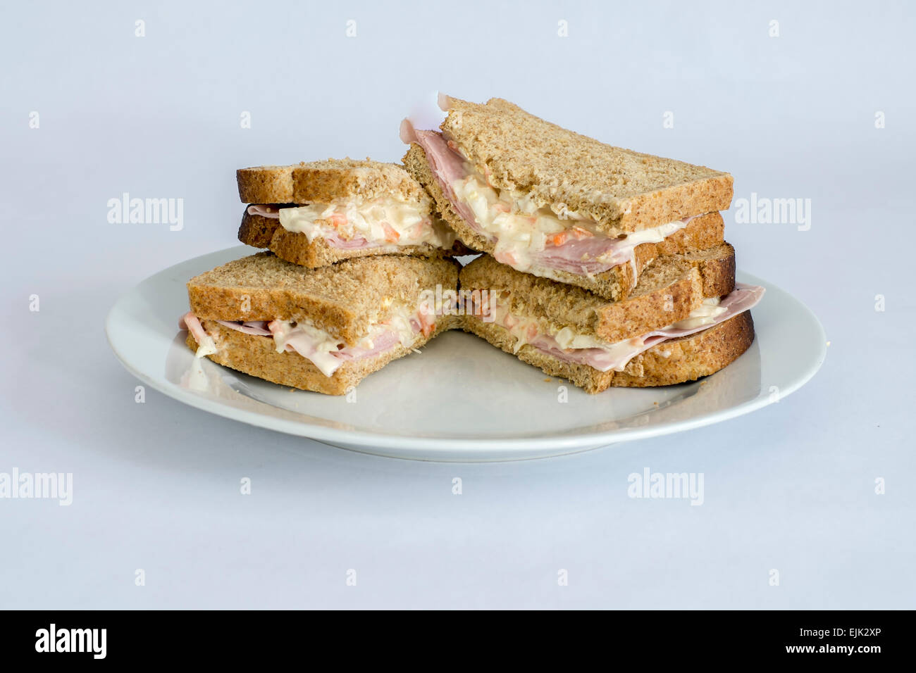 Ham & coleslaw sandwich on a white plate with white back ground - Stock Image