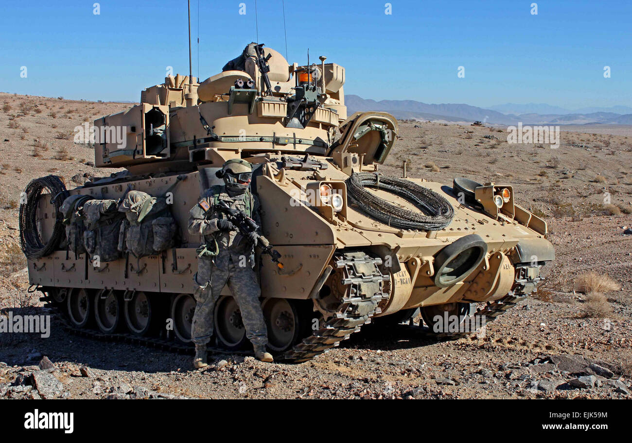 U.S. Army soldier from the 3rd Armored Brigade Combat Team, 1st Infantry Division pulls security next to a M2 Bradley - Stock Image