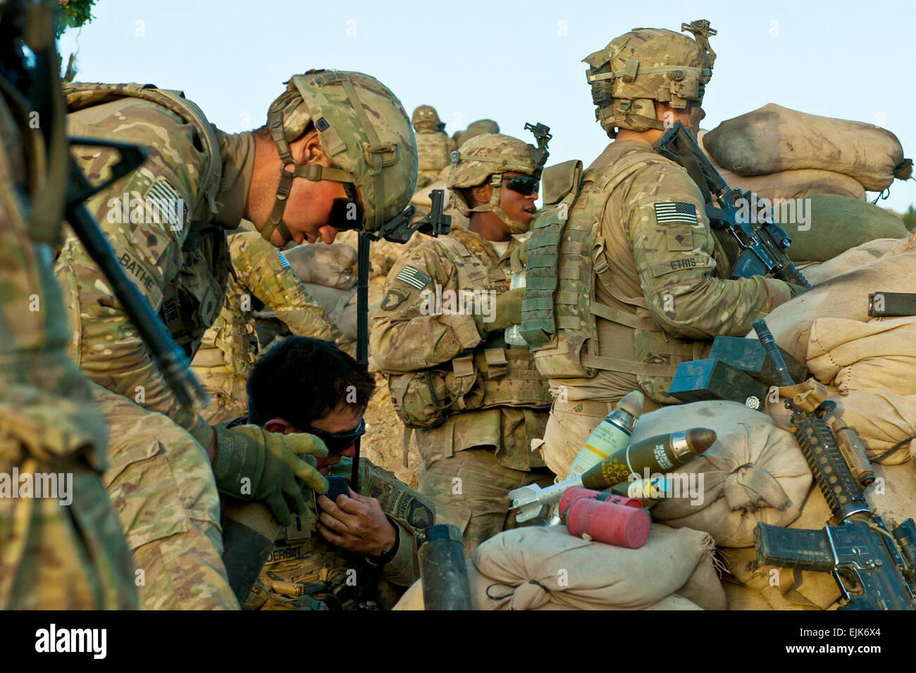 U.S. Army Soldiers consolidate rounds and watch for enemy activity following a machine-gun and small arms attack - Stock Image