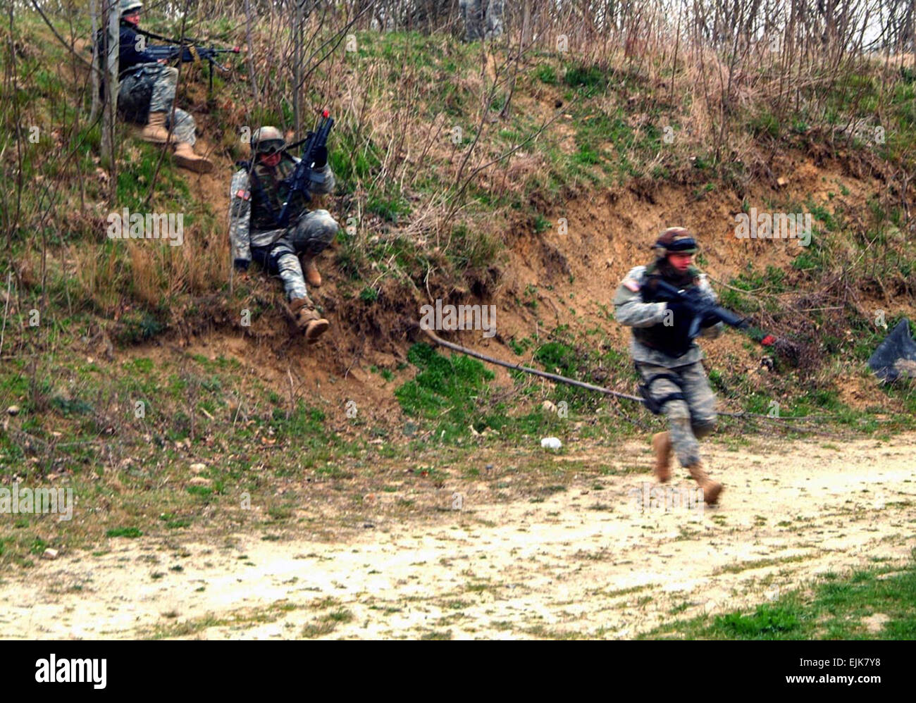 U.S. Army Soldiers from the 501st Military Police Company scramble down a berm toward their objective during squad - Stock Image