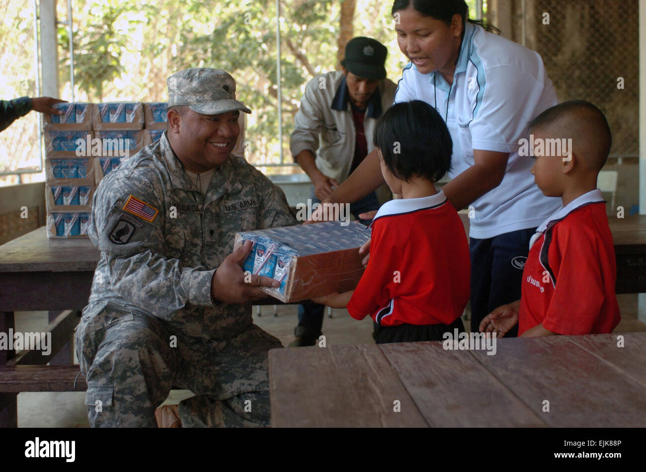 Spc. Andrew Kalaukoa of Makaha, Hawaii, distributes milk to the children of the Ban Pong Wua School in rural Thailand - Stock Image