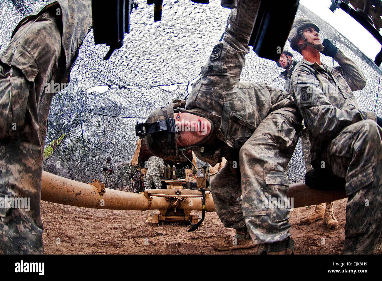 Spc. Michael Davis, center, checks the breech of an M119A2 105mm  lightweight howitzer