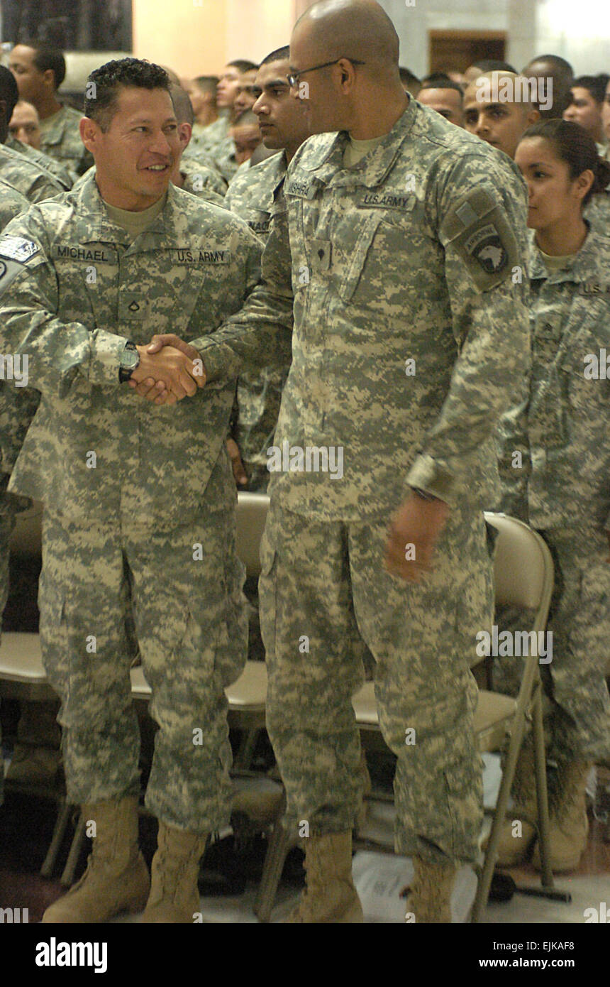 Spc. Vivek Mishra right with the 101st Airborne Division, shakes hands with Pfc. Henry Michael, 72nd Military Police - Stock Image