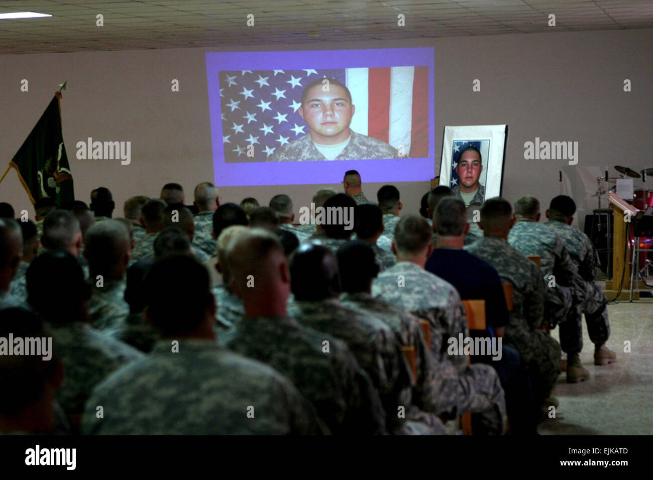 Service members watch a slide show in honor of Army Pfc. Aaron Ward during a memorial service at the chapel on Al - Stock Image