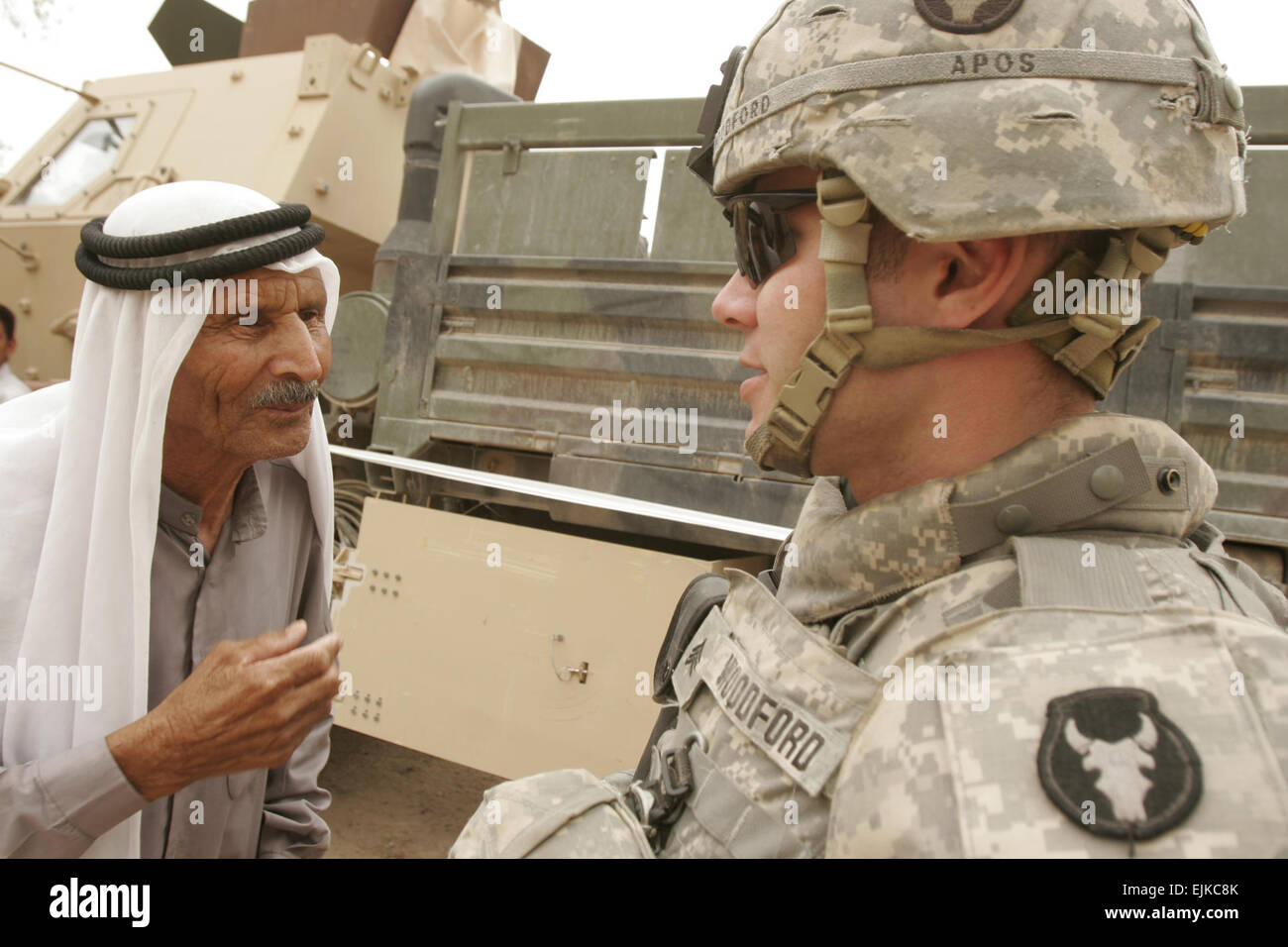 U.S. Army Sgt. Jeff Woodford speaks with an Iraqi man waiting to receive medical care during a cooperative medical - Stock Image