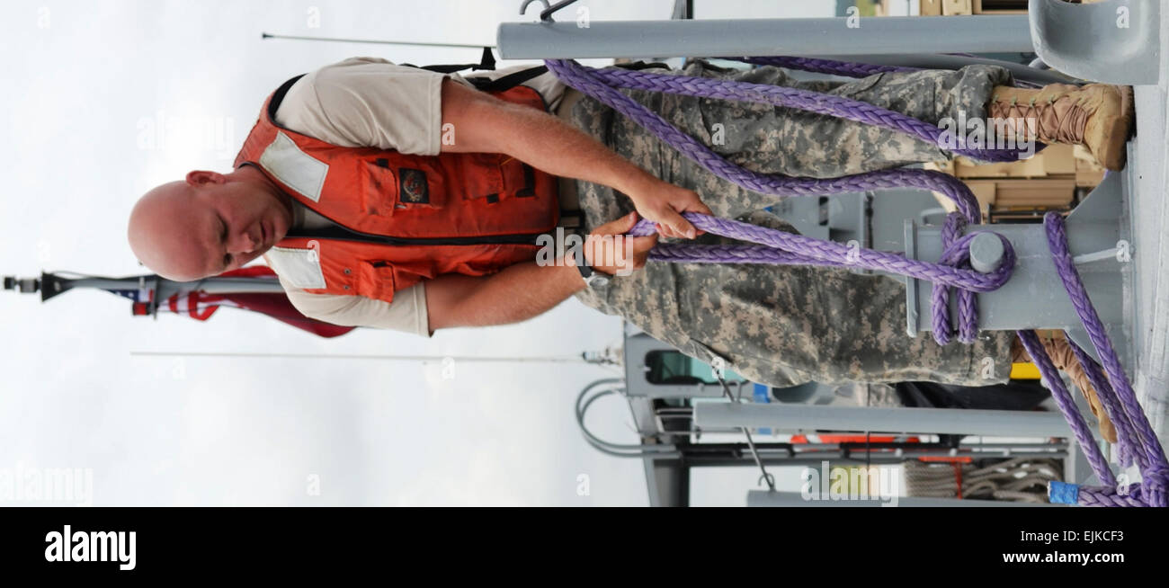 A 7th Sustainment Brigade soldier secures the ties to his mike boat while docking during a Joint Logistics Over - Stock Image