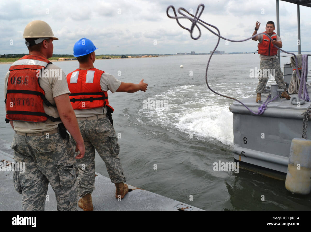 Pfc. Juan Guebara, right, a watercraft engineer assigned to the 7th Sustainment Brigade, tosses a line to two soldiers - Stock Image