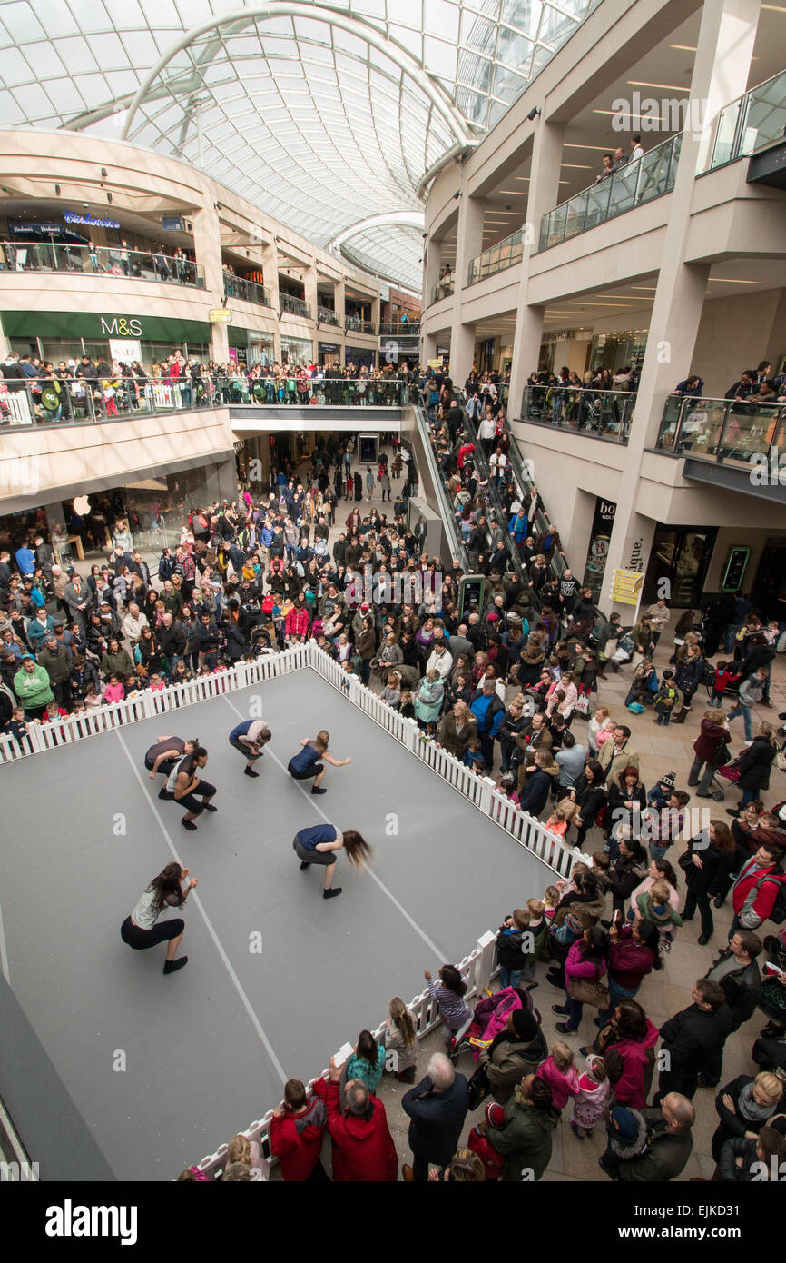 Shoppers and a street performer dancing in Trinity shopping centre, Leeds - Stock Image