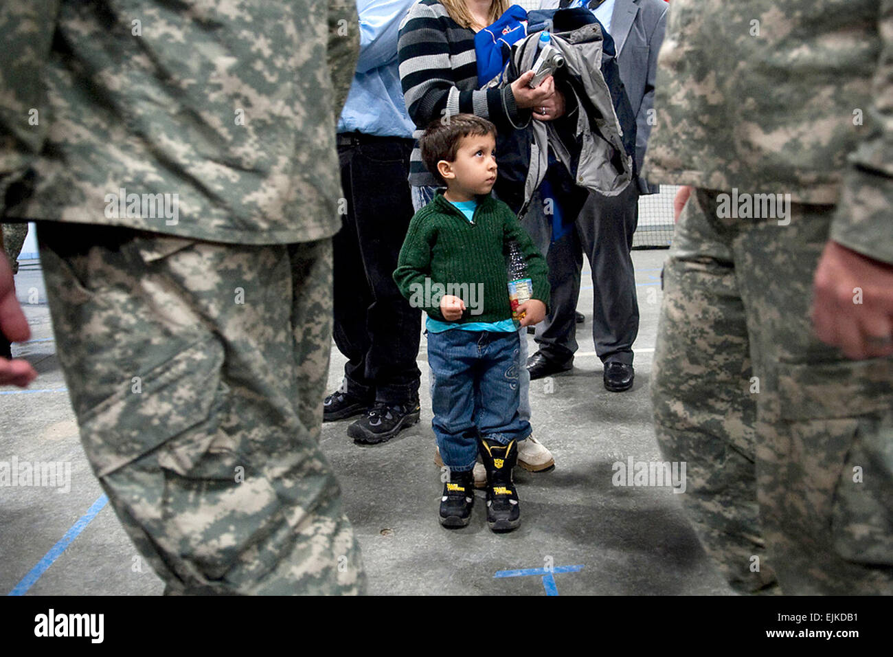A young boy watches Soldiers of the 86th Infantry Brigade Combat Team leave after their departure ceremony in Burlington, - Stock Image