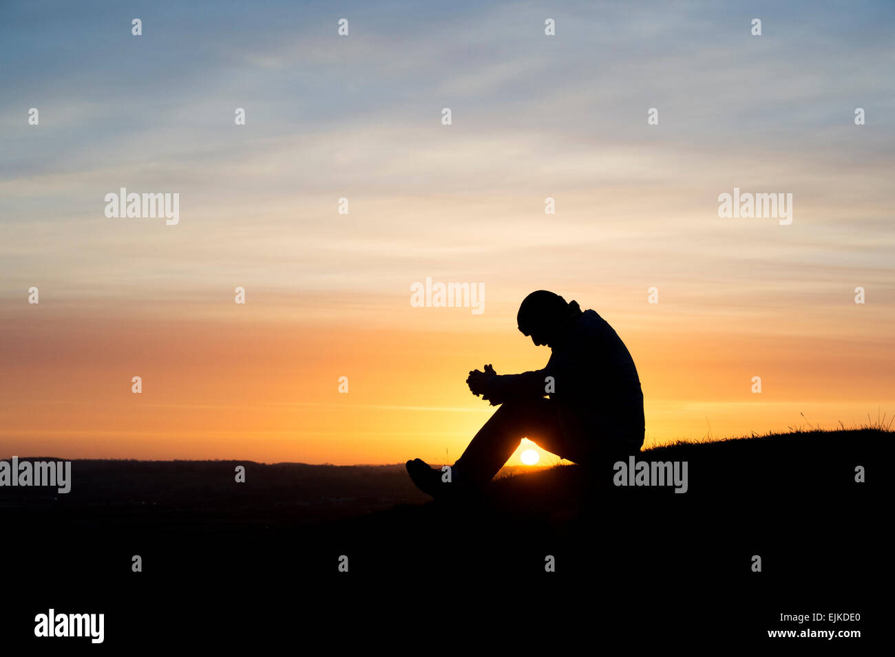 Thoughtful man sitting on a hillside at sunrise. Silhouette Stock Photo