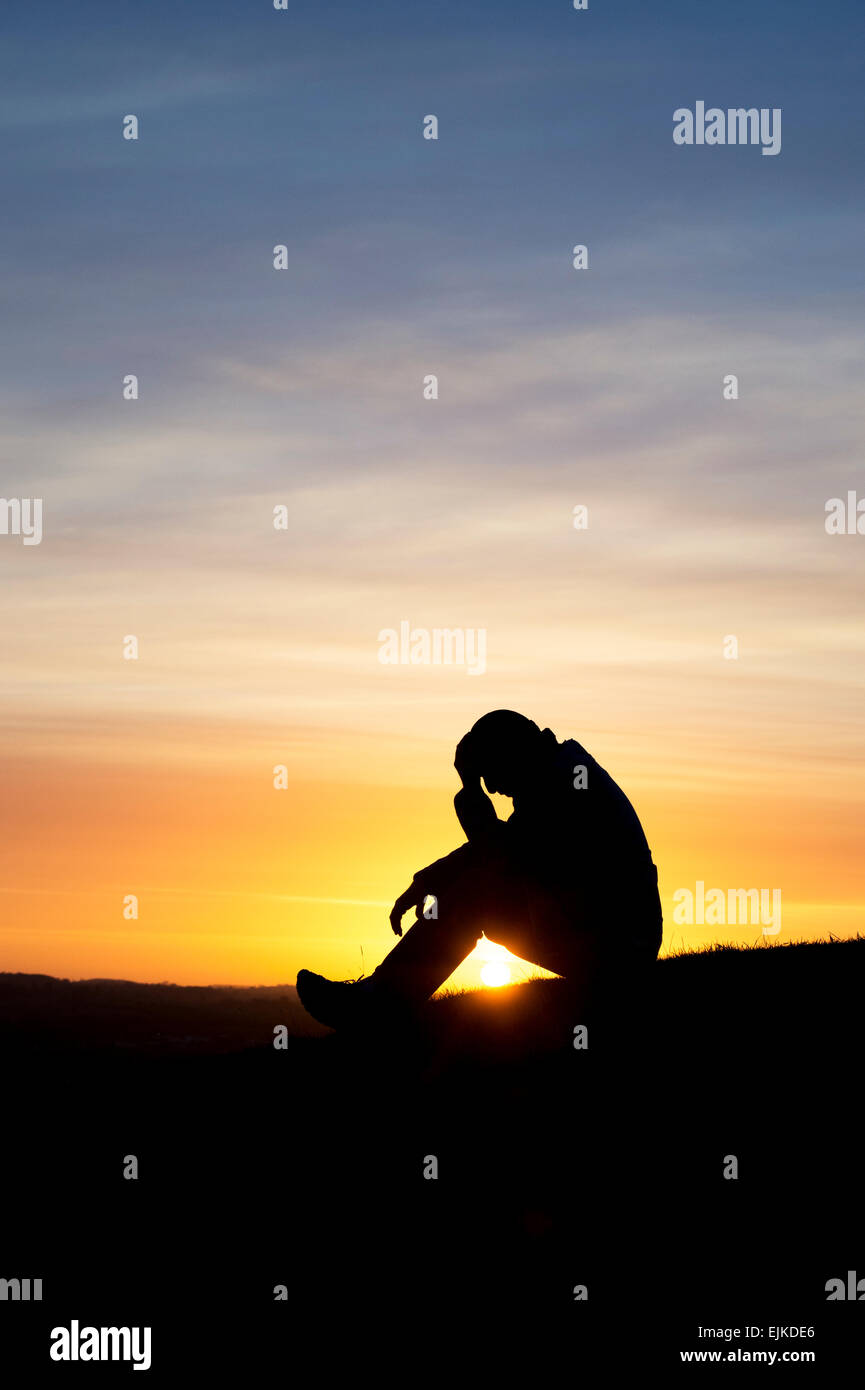 Worried man sitting on a hillside at sunrise. Silhouette Stock Photo
