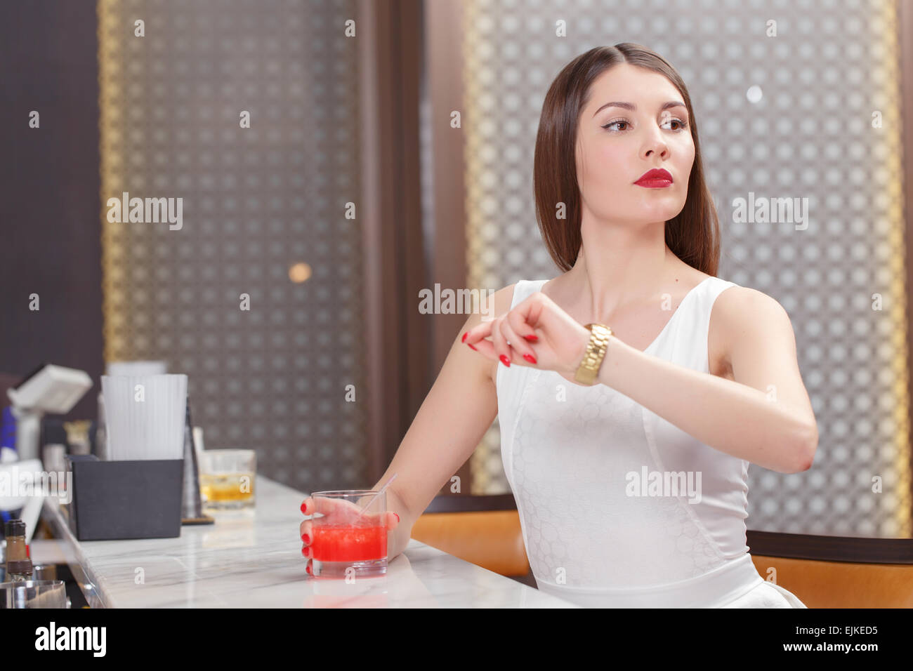 Woman looks at her watch - Stock Image