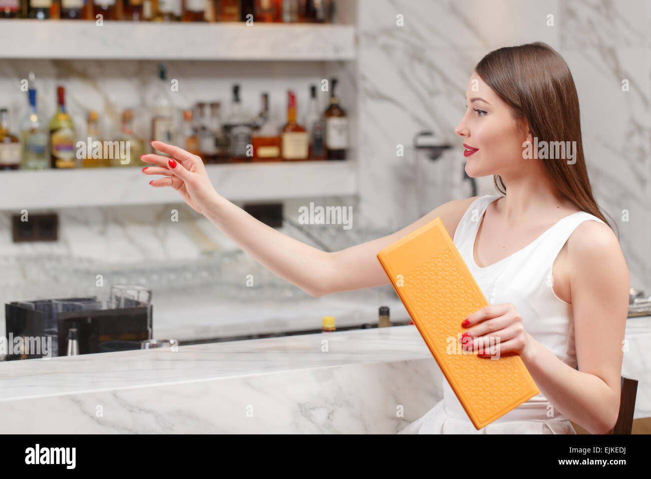 Woman holds a menu at the bar - Stock Image