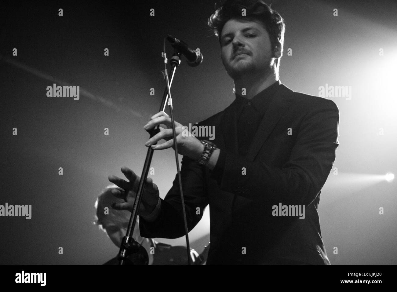 Man posed in between singing in a band and looking directly at the camera almost playing the microphone as if it's - Stock Image