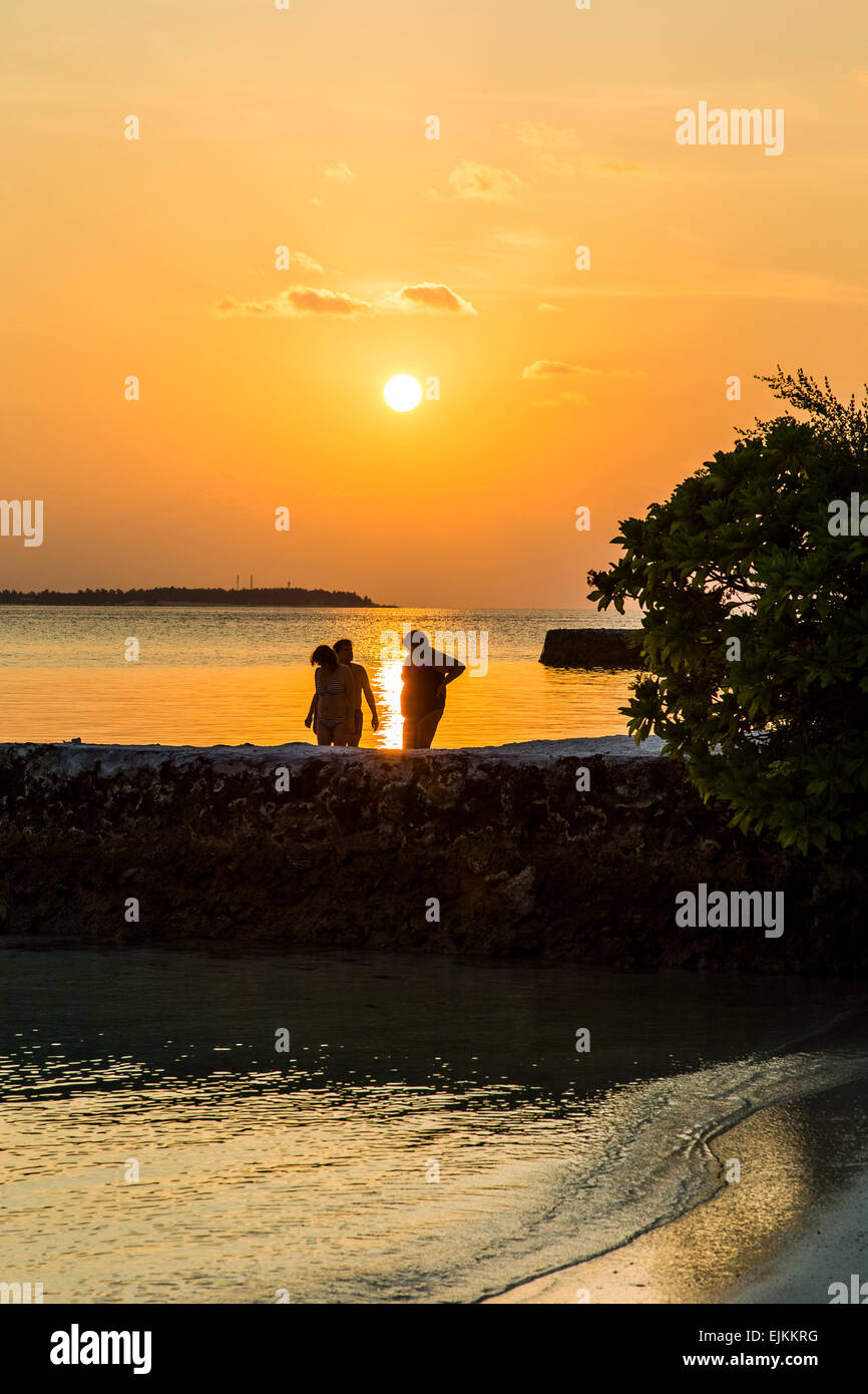 People paddling in the sea at sunset on the island of Makunudu in the Maldives Stock Photo