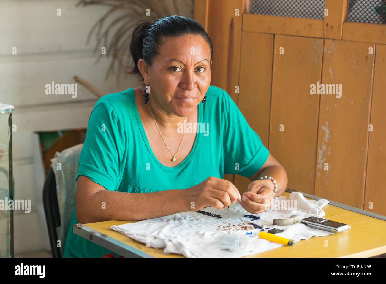 Amerindian woman making jewellery, Galibi, Suriname - Stock Image