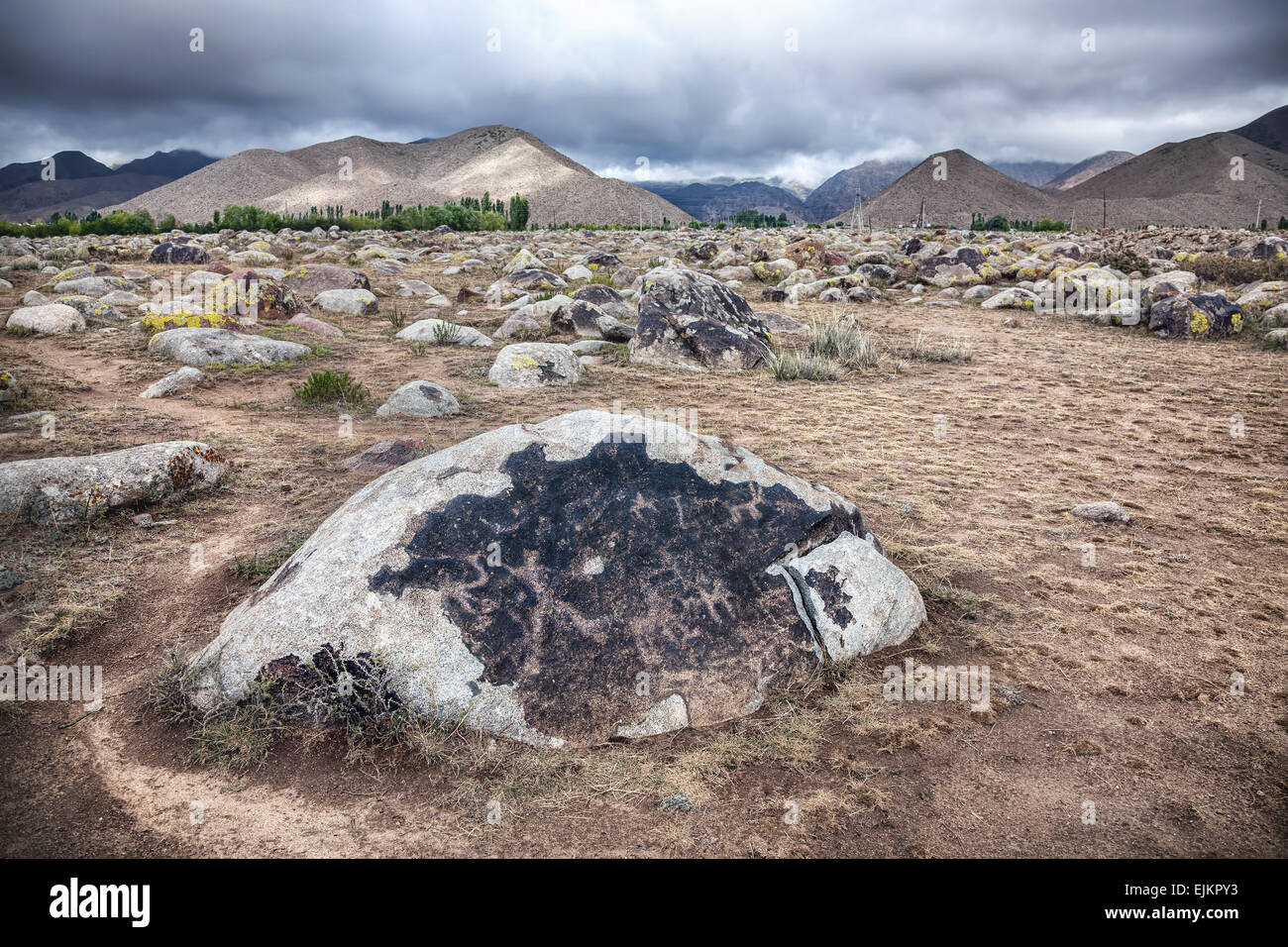 Ancient petroglyph with hunter and animals on the stone in open air museum of Kyrgyzstan at overcast mountain background - Stock Image