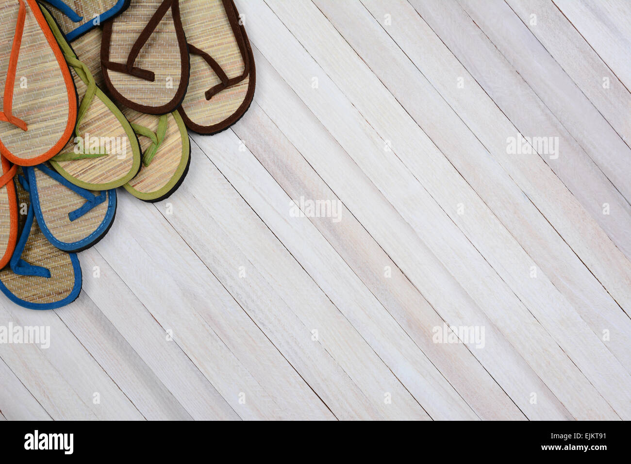 Summer sandals on a rustic white wood surface. The flip flops are set in the upper left side and corner of the frame - Stock Image