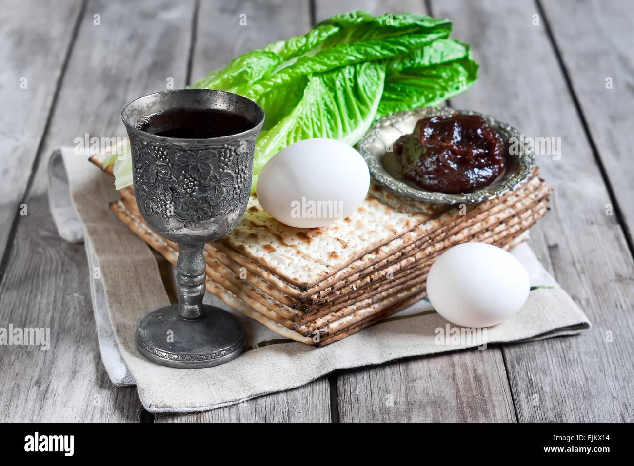 Wine, egg, bitter salad leaves, matzot and haroset - traditional jewish passover celebration elements. - Stock Image