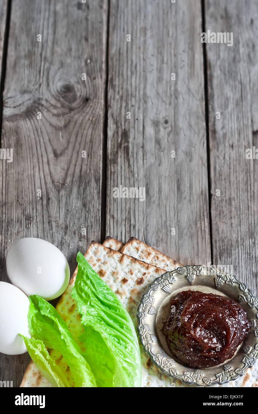 Egg, bitter salad leaves, matzot and haroset - traditional jewish passover celebration elements. Copy space background. - Stock Image