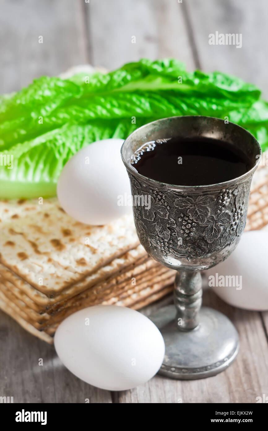 Wine, egg, bitter salad leaves, matzot - traditional jewish passover celebration elements. - Stock Image