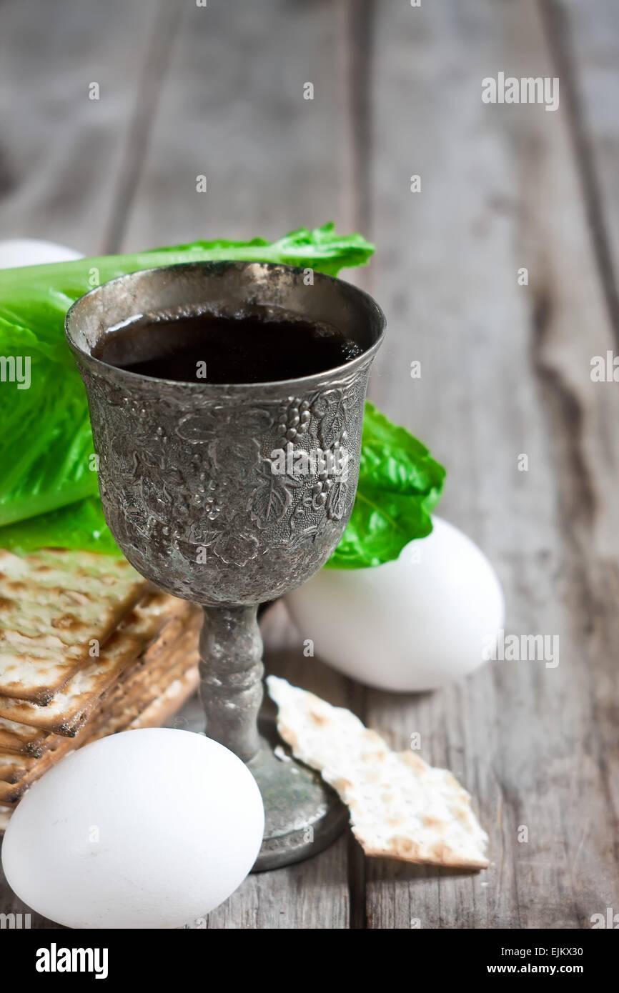 Wine, egg, bitter salad leaves, matzot - traditional jewish passover celebration elements. Copy space background. - Stock Image