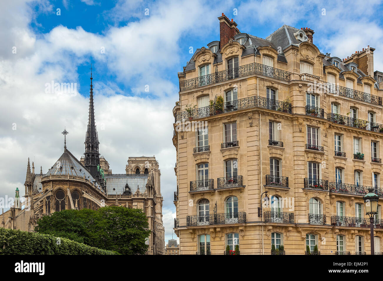 View on typical parisian building as Notre Dame de Paris Cathedral on background. - Stock Image
