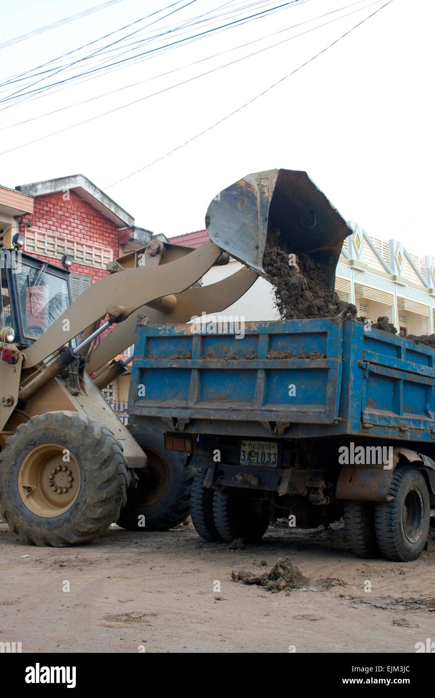 A skip loader is dumping dirt into a dump truck on a city street in Kampong Cham, Cambodia. - Stock Image