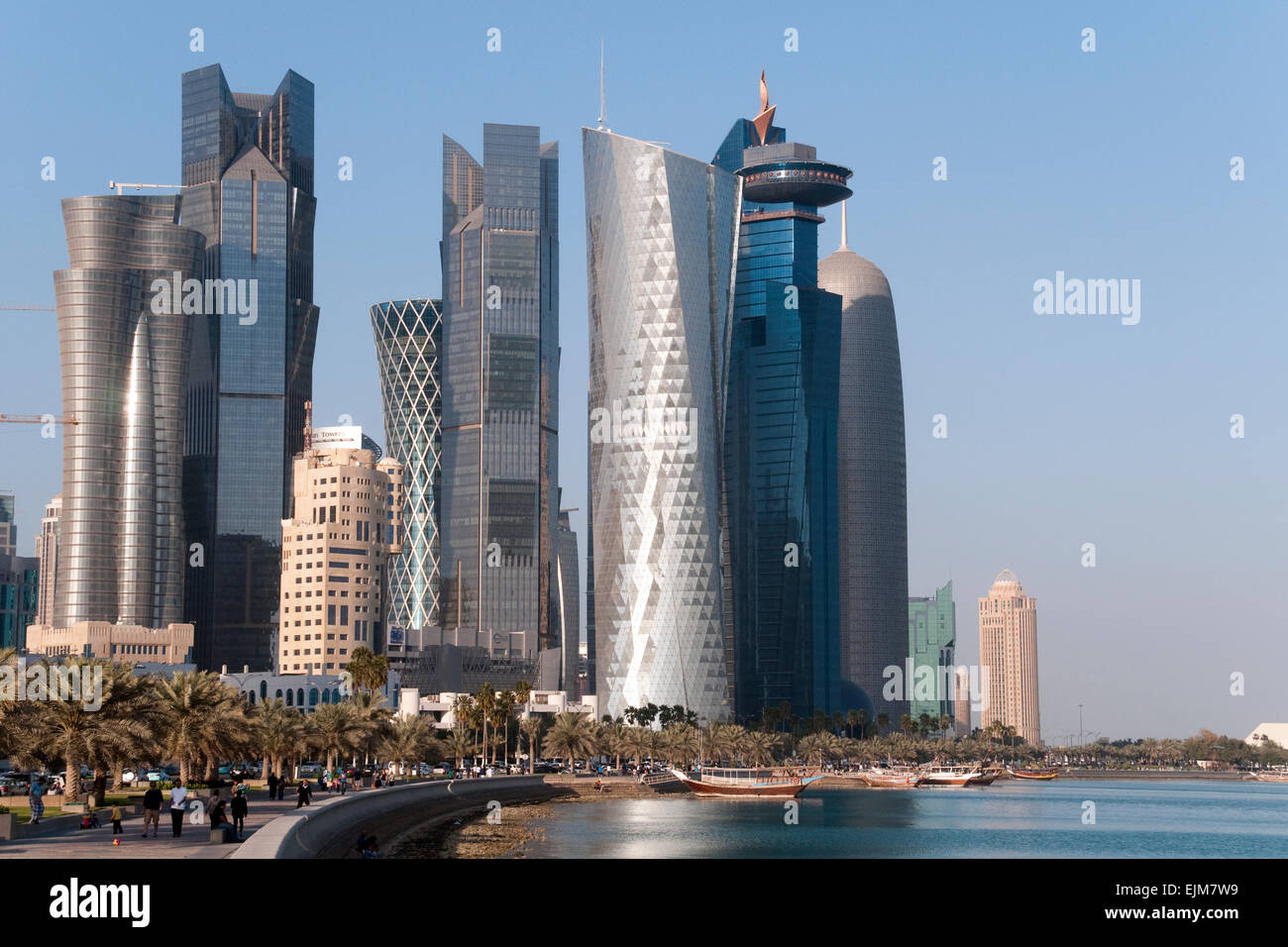 Pedestrians walk the waterfront corniche, below skyscrapers, in the city of Doha in the gulf state of Qatar. Stock Photo