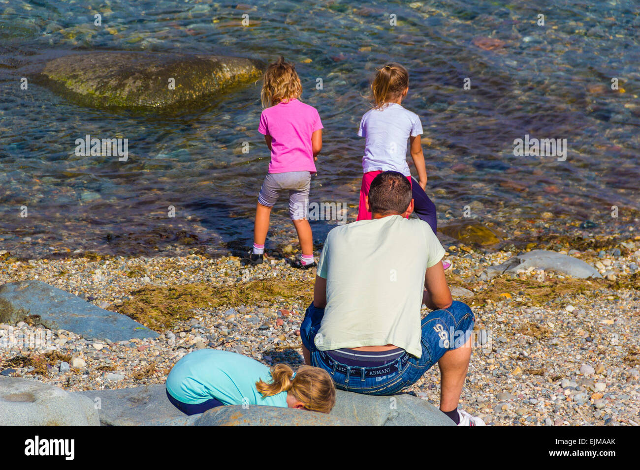 Three toddler girls playing in a sea at Welsh town of Criccieth watched over by the father. Stock Photo