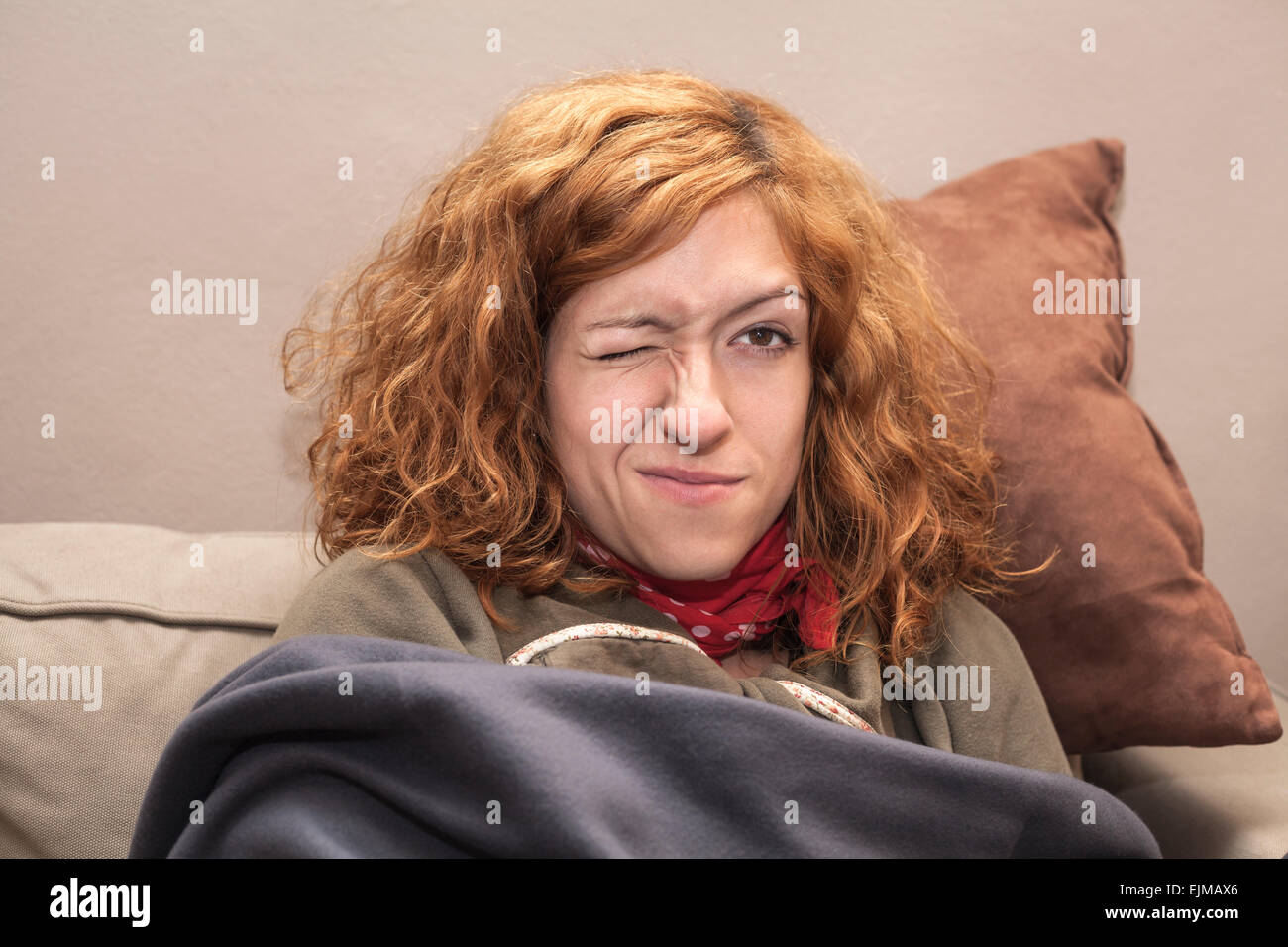 Closeup of a redhead woman face with one eye closed, relaxing on the sofa at home. - Stock Image