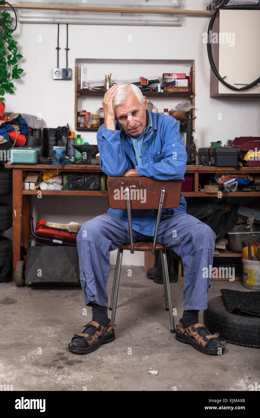 Portrait of frustrated senior worker sitting on the chair in his workshop. - Stock Image