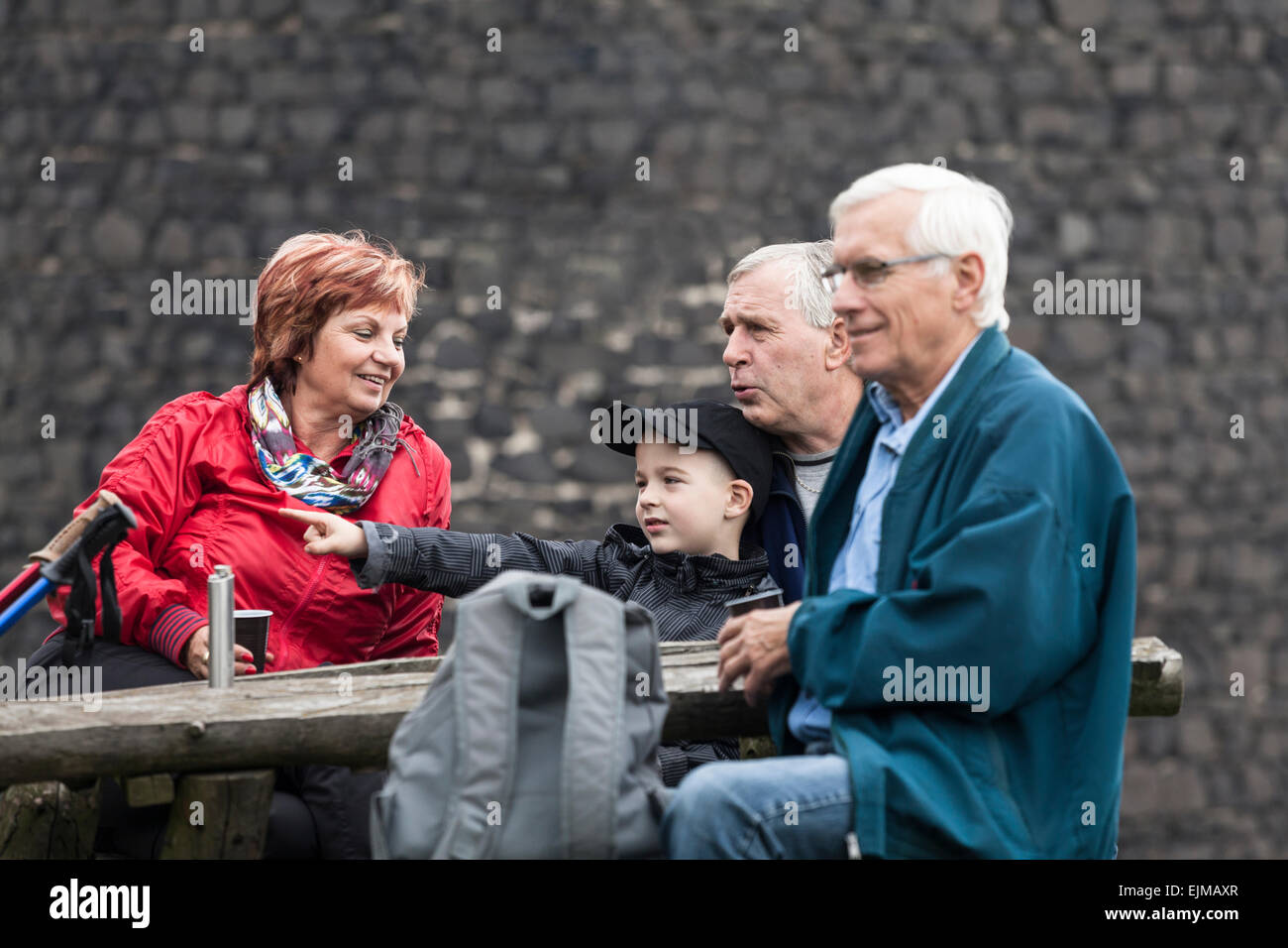 Seniors with child on family hiking trip relaxing outdoors. - Stock Image