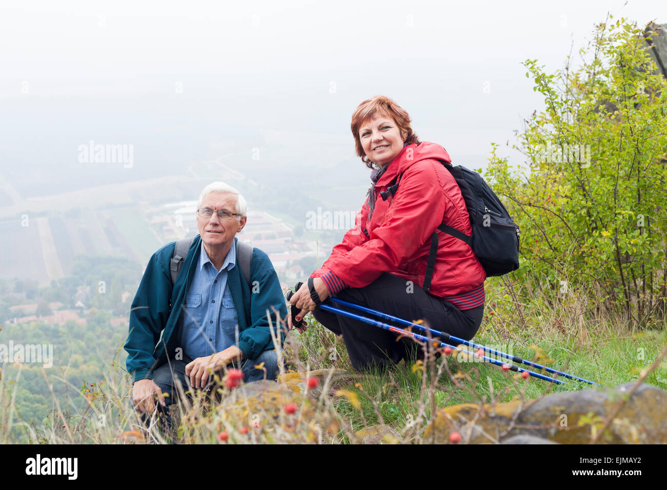 Senior couple on hiking trip resting in the nature. - Stock Image
