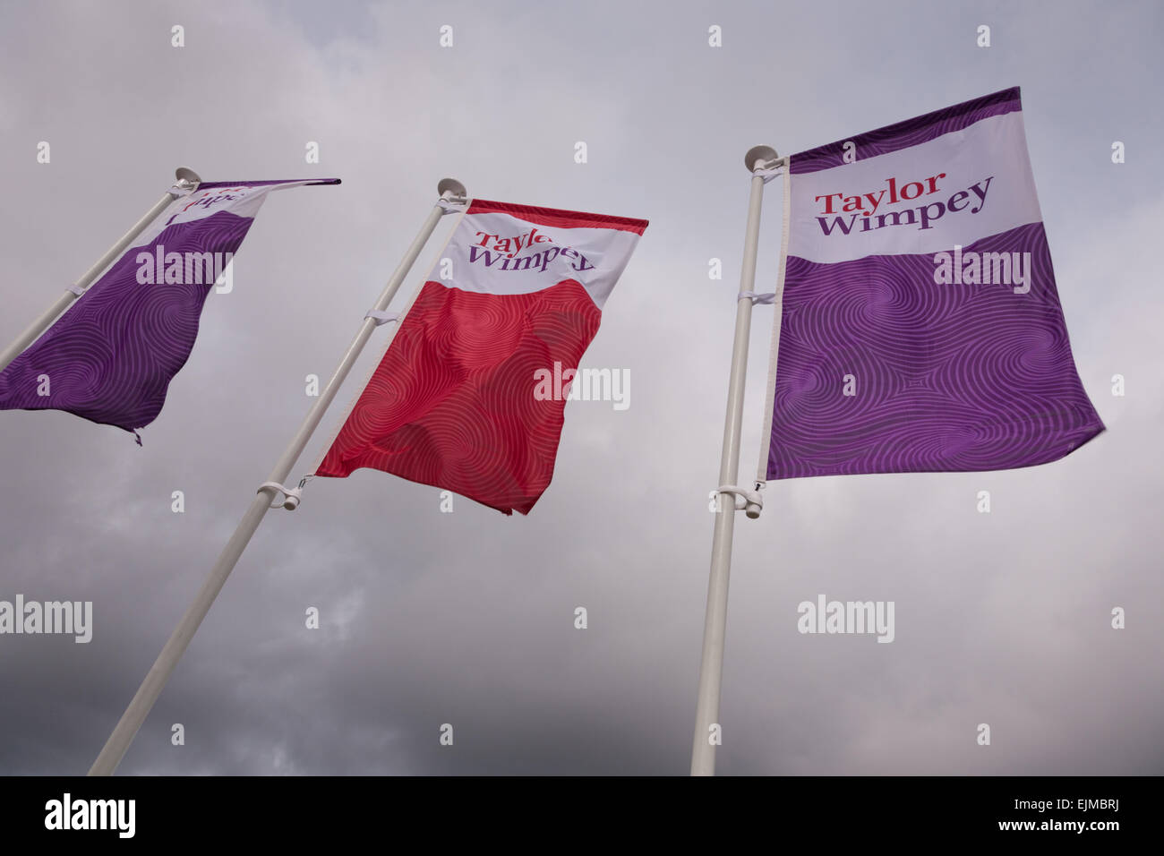 Promotional flags for Taylor Wimpey property developers flying at a new site - Stock Image