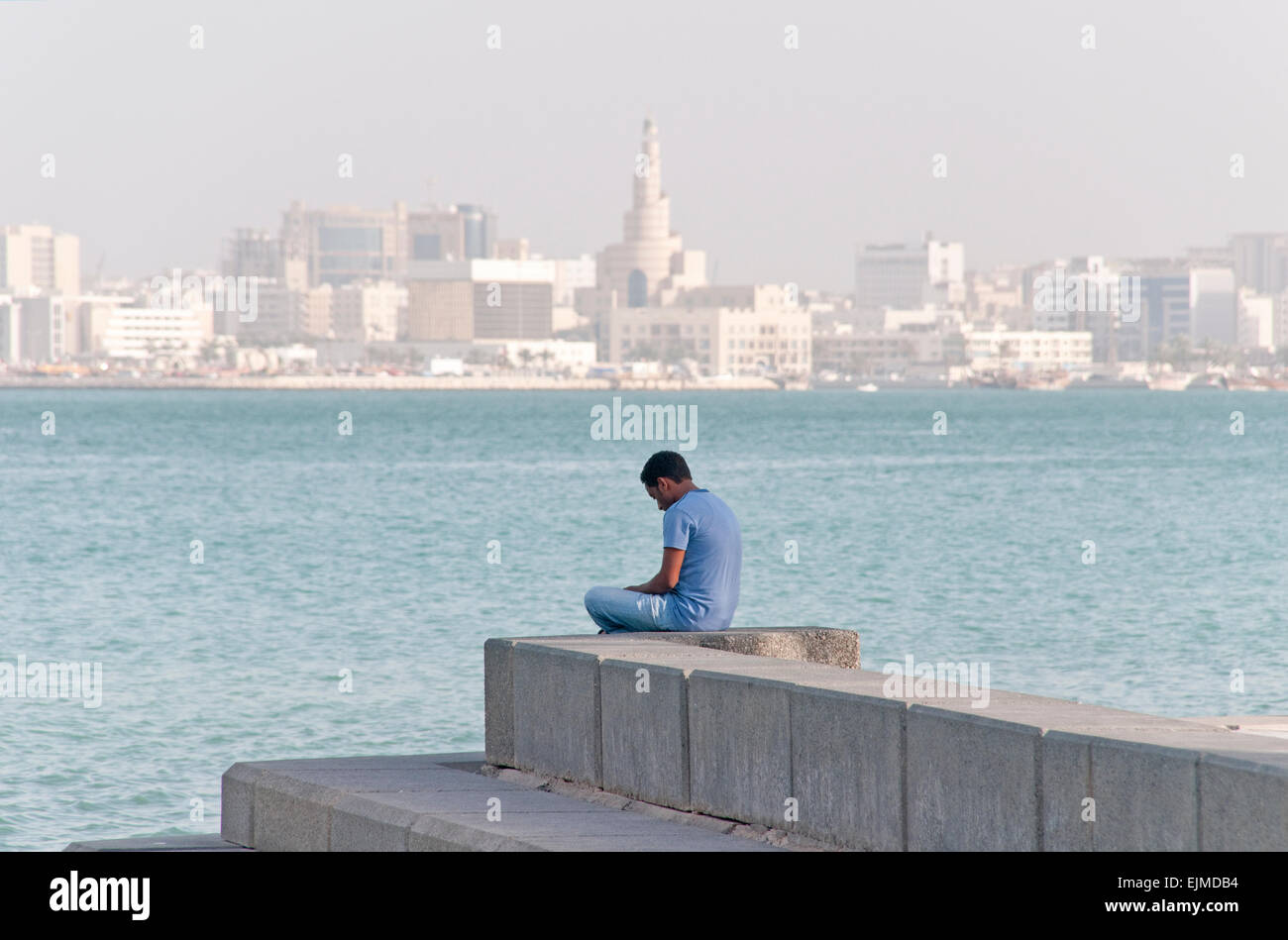A man sits alone in Doha, Qatar, with the cityscape and Arabian Gulf in the background. Stock Photo