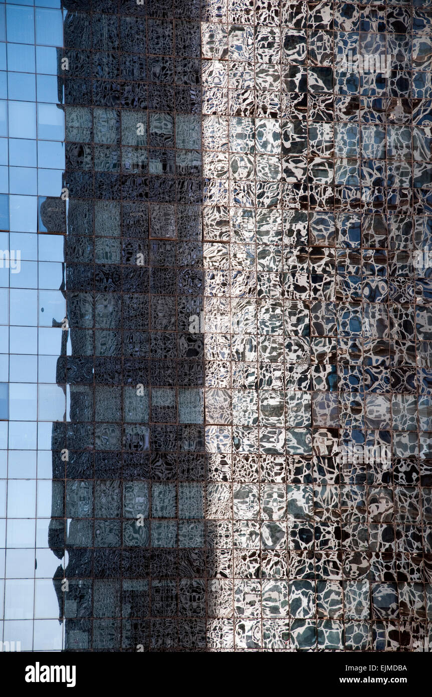 The exterior of the Doha Tower reflected in the window of a neighboring skyscraper in the city of Doha, Qatar. - Stock Image
