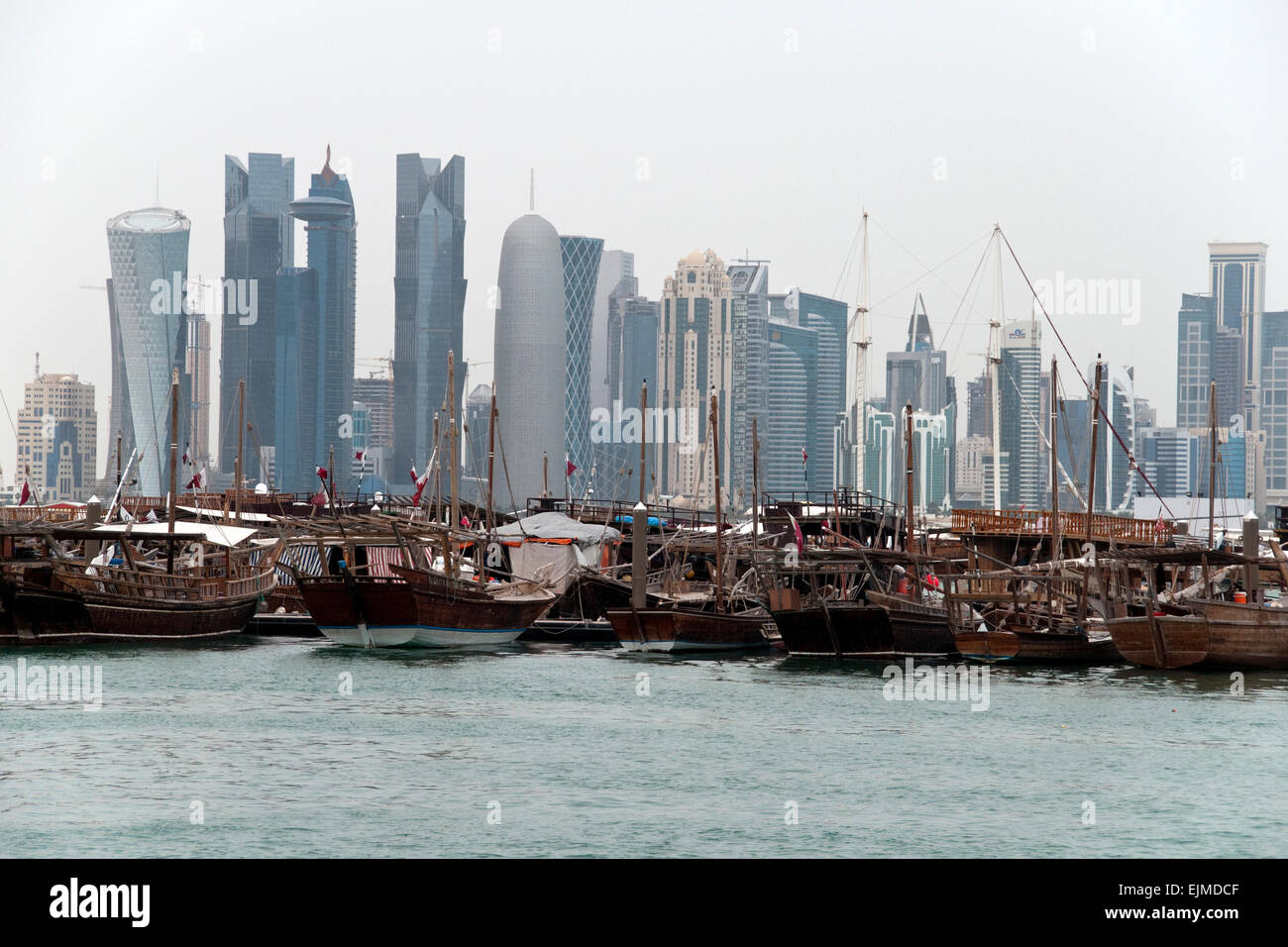 A fleet of dhow boat docked in a port, with the skyline of Doha, Qatar, in the background. Stock Photo