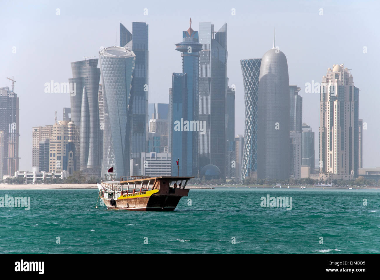 A dhow boat plows the waters of the Arabian Gulf near the skyline of Doha, the capital of Gulf nation of Qatar. Stock Photo