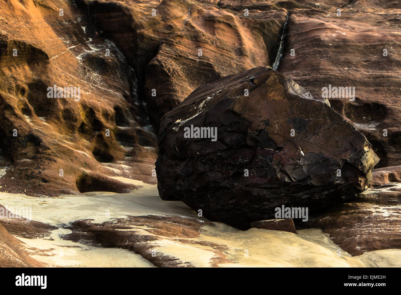 Abstract rock and rock wall on hues of red and sand on the ground - Stock Image