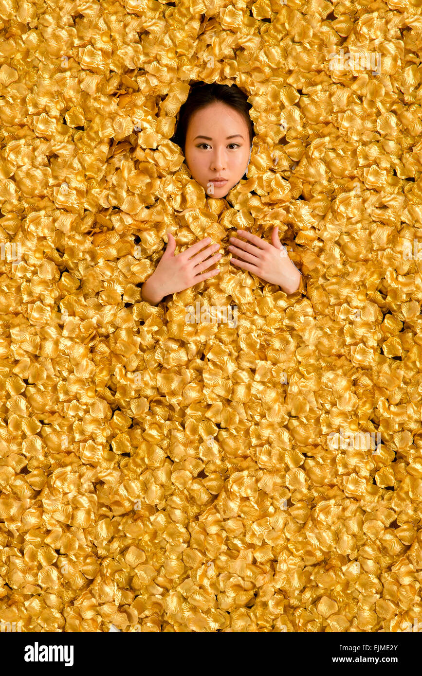 Luxury: A young ethnic chinese woman girl lying in a bath  surrounded encased by thousands of golden gold petals - Stock Image