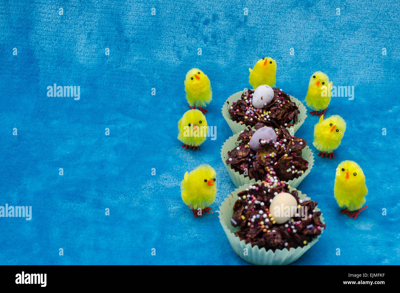 Perfect picture for celebrating Easter. Three cornflake cakes in a row are surrounded by little baby yellow toy - Stock Image