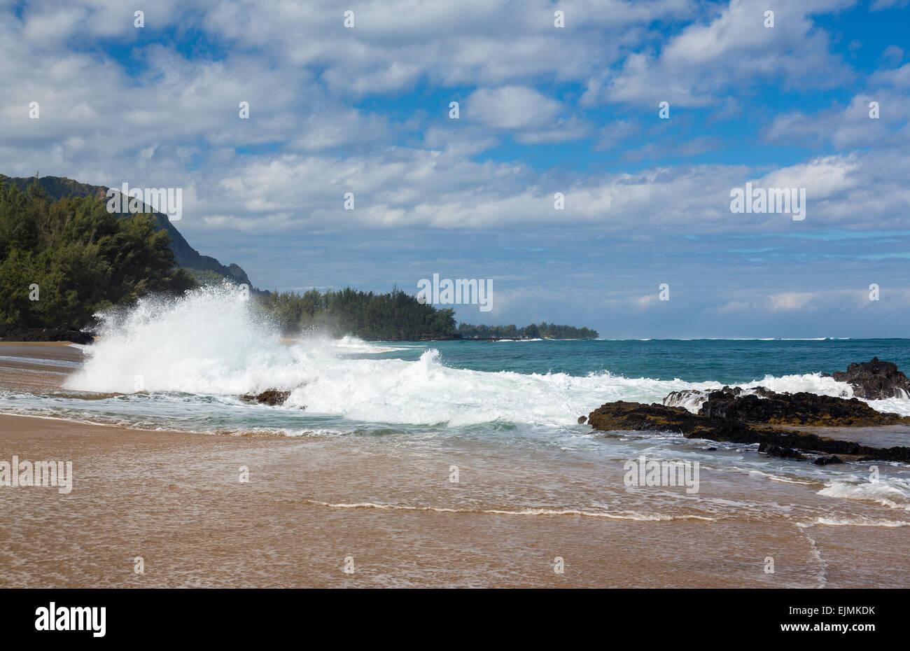 Waves crash onto Lumahai beach with Na Pali range in background on Kauai Hawaii - Stock Image