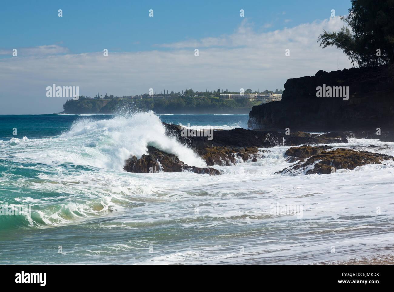 Waves crash onto Lumahai beach with St Regis hotel in background on Kauai Hawaii - Stock Image