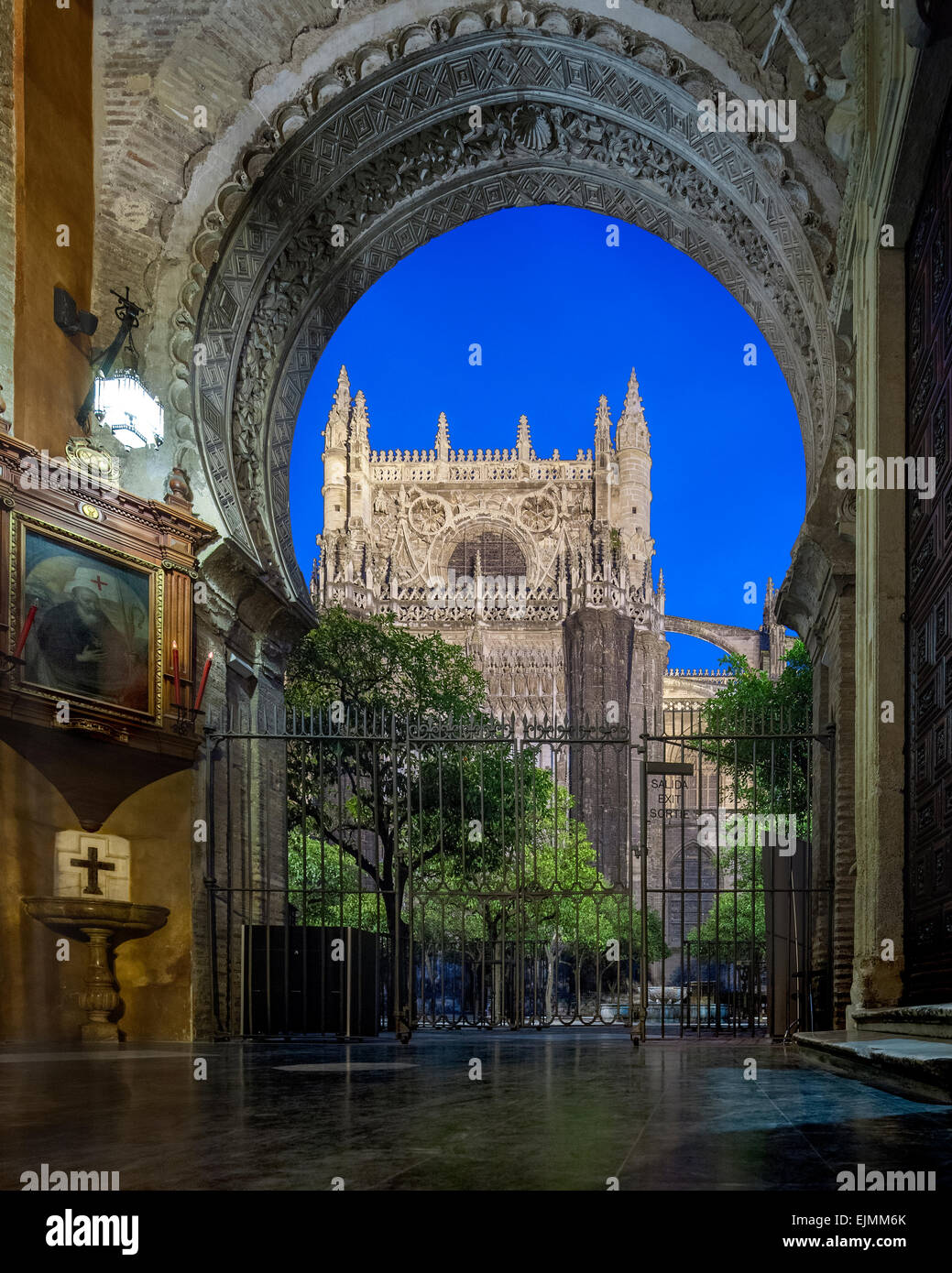 Seville Cathedral at night from the Door of Forgiveness former Almohad mosque gate and the Patio de los Naranjos - Stock Image